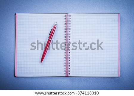 Composition of red ball-point pen open copybook office concept. - stock photo