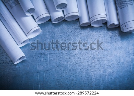 Composition of rolled construction plans on scratched silver-metal surface building and architecture concept. - stock photo