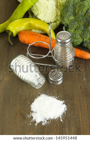 Composition of salt and pepper mills and fresh vegetables, on wooden background - stock photo