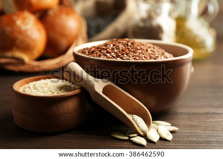 Composition of sesame, flax, pumpkin seeds and buns on wooden table background, closeup - stock photo