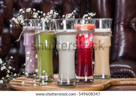 Composition of smoothies in glass on cutting board in luxury restaurant interior with flowers. Close-up view.