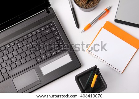 Composition of some office equipments on a desk, overhead shot over white background - stock photo
