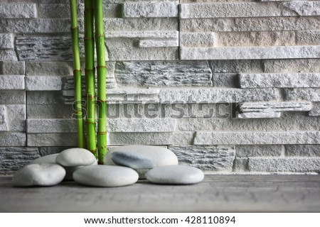 Composition of spa pebbles and bamboo on grey wall background - stock photo