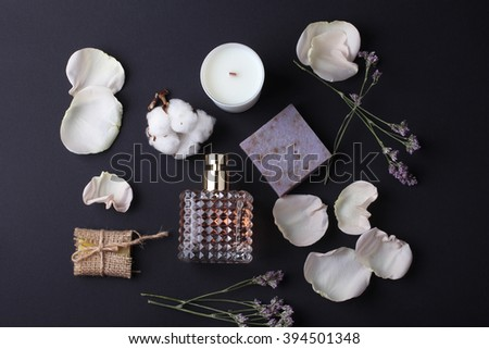 Composition of spa treatment and perfume on black table with flowers. - stock photo