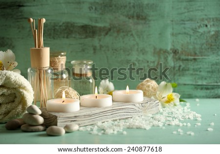 Composition of spa treatment, candles in bowl with water on wooden background - stock photo