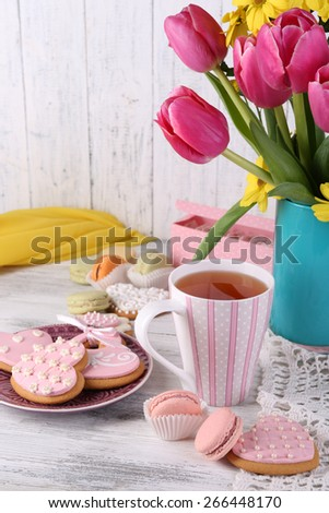Composition of spring flowers, tea and cookies on table close-up - stock photo