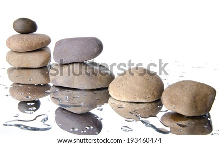 Composition of stacked pebbles, on a white wet background - stock photo
