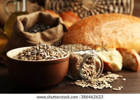 Composition of sunflower seeds and bread on wooden table background, closeup
