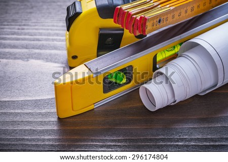 Composition of tape-measure blueprints construction level and wooden meter on vintage wood board maintenance concept. - stock photo