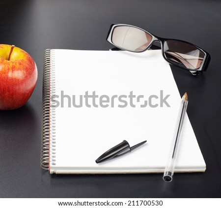 Composition of the red apple, glasses and opened copyspace empty note book over the black background - stock photo