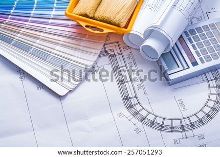 composition of tools stack rolled up white blueprints calculator paintbrushes in paint can
