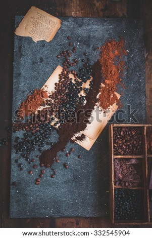 Composition of various coffee beans and cacao powder slicing chocolate on a blue stone table. Dark rural still life  - stock photo