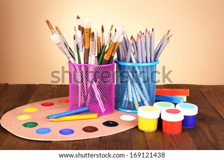 Composition of various creative tools on table on beige background - stock photo