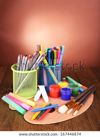 Composition of various creative tools on table on brown background
