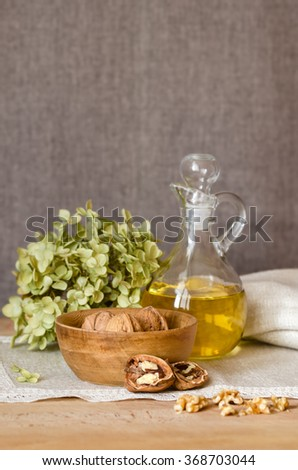 Composition of walnuts and walnut oil on a wooden table