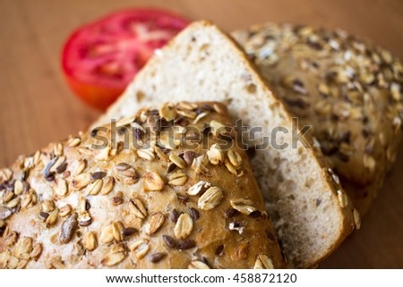 Composition of whole grain bread buns and tomato on wooden table background