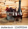 composition of wine,basket and grapes on table on brick wall background - stock photo