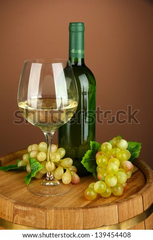 Composition of wine bottle, glass of white wine, grape on  wooden barrel, on color background