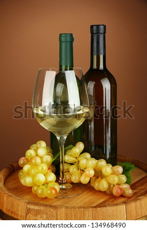 Composition of wine bottles, glass of white wine, grape on  wooden barrel, on color background