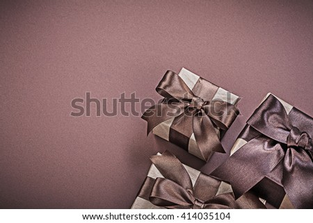 Composition of wrapped giftboxes on brown surface holidays concept.