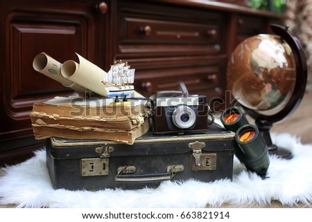 composition on a wooden floor vintage globe with old leather suitcase with objects for travel