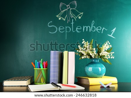 Composition on desk with books and flowers on green blackboard with inscription on background - stock photo