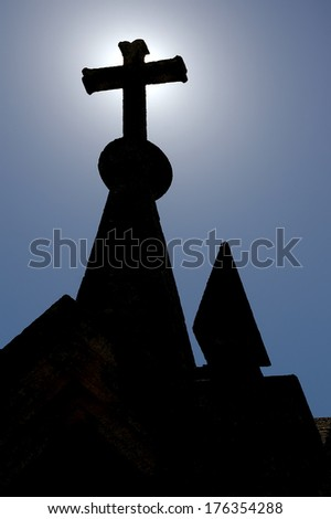Composition with a backlit stone cross against a blue sky. - stock photo
