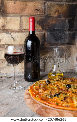 Composition with a pizza, wine and oil on a firebricks background - stock photo