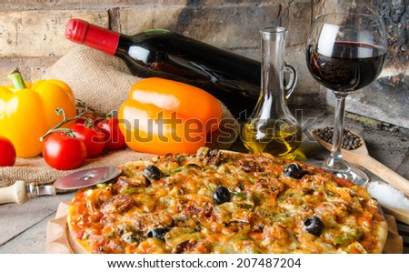 Composition with a pizza, wine and some ingredients on a firebricks background - stock photo