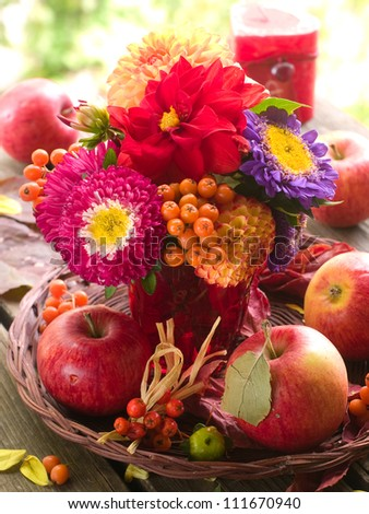 Composition with an autumn apples, flowers and rowan, selective focus - stock photo