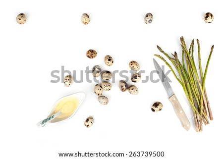 Composition with asparagus, quail eggs and pitcher with mustard mayonnaise over white background, above view. - stock photo
