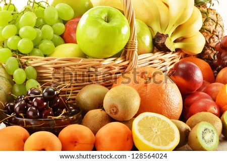 Composition with assorted fruits in wicker basket isolated on white - stock photo