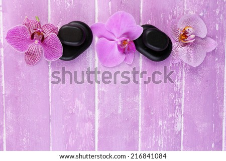 Composition with beautiful blooming orchids and spa stones on color wooden background  - stock photo