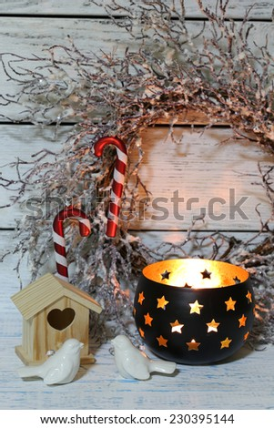 Composition with beautiful candlesticks, Christmas wreath and other decorations for home interior on wooden background - stock photo