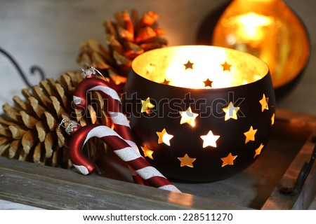 Composition with beautiful candlesticks, cones and other decorations for home interior on wooden background - stock photo