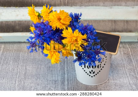 Composition with blue and yellow colors of wild flowers in a decorative vase with tablet for text