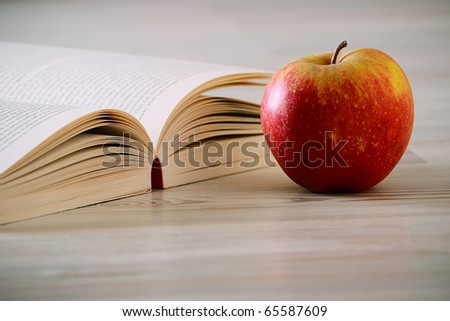 Composition with book and apple on the wooden table