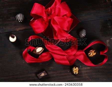 composition with box, chocolate candies and red ribbon shaped as hearts on a wooden old background, top view - stock photo