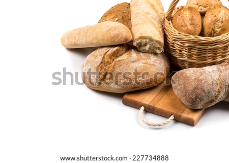 Composition with bread and rolls in wicker basket isolated on white - stock photo
