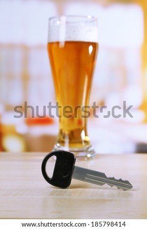 Composition with car key and glass of beer, on wooden table, on bright background