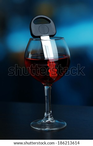 Composition with car key and glass of red wine, on wooden table, on bright background - stock photo