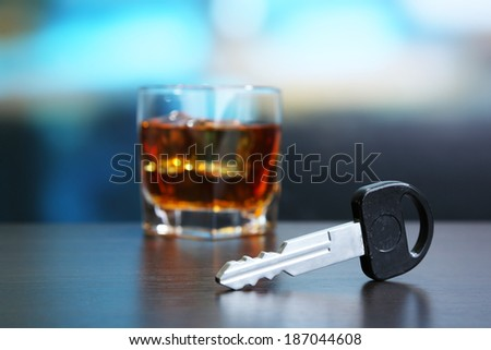 Composition with car key and glass of whiskey, on wooden table, on bright background - stock photo