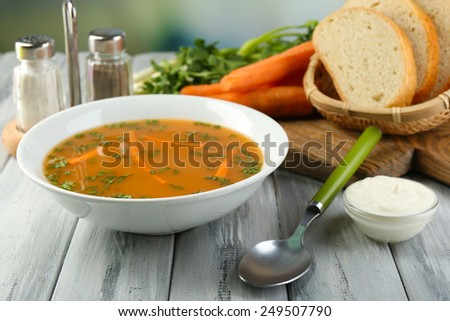 Composition with carrot soup, ingredients and herbs on color wooden table, on light background - stock photo