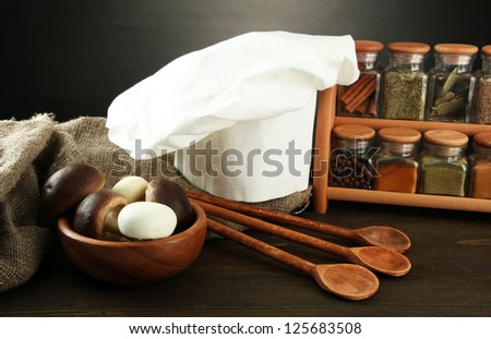 Composition with chef's hat and kitchenwear on table on grey background - stock photo