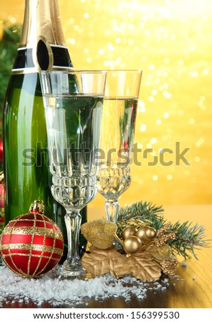 Composition with Christmas decorations and two champagne glasses, on bright background