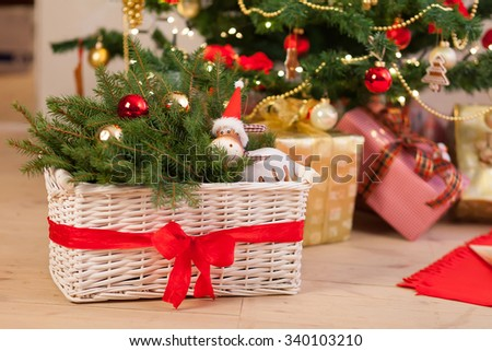Composition with Christmas decorations in basket, fir tree on wooden floor - stock photo