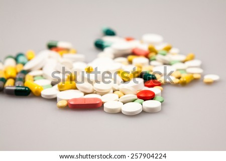 Composition with colorful pills and light grey background