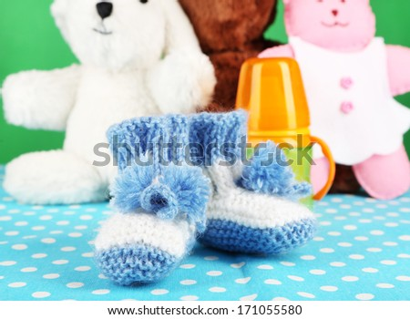 Composition with crocheted booties for baby, bottle, toy and other things on color background - stock photo
