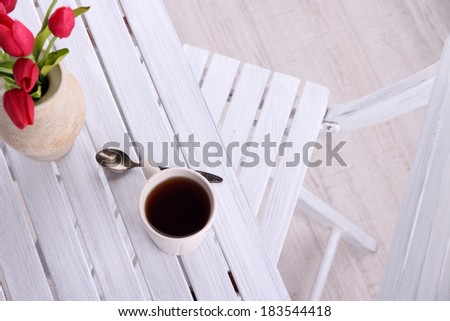 Composition with cup of hot drink, candle and flowers on wooden table background - stock photo