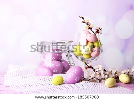 Composition with Easter eggs and blooming branches on light background - stock photo